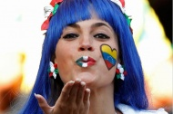 A fan blows a kiss to the photographer as she waits for the start of the World Cup Group F between Italy and New Zealand.